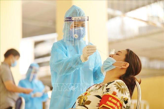 Nhân viên Trung tâm y tế quận Hai Bà Trưng phối hợp với y tế phường Bạch Mai lấy mẫu xét nghiệm COVID-19 cho các trường hợp thuộc khu vực có nguy cơ cao. Ảnh: Minh Quyết/TTXVN.