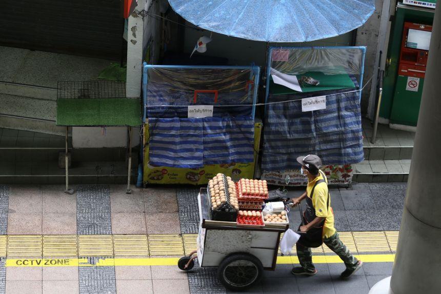 Một người bán trứng đi qua khu chợ đóng cửa ở Bangkok, Thái Lan. Ảnh: Straits Times