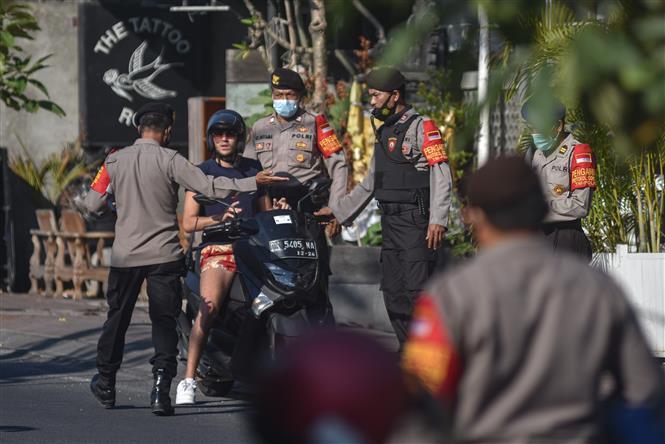 Cảnh sát nhắc nhở một du khách nước ngoài đeo khẩu trang phòng lây nhiễm COVID-19 tại Bali, Indonesia. Ảnh: AFP/TTXVN