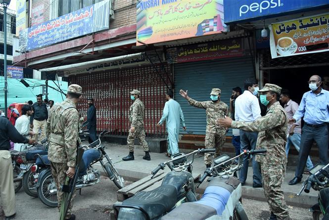 Binh sĩ quân đội Pakistan tuần tra nhắc nhở người dân thực hiện các quy định nhằm ngăn chặn sự lây lan của dịch COVID-19 tại Karachi. Ảnh: THX/TTXVN