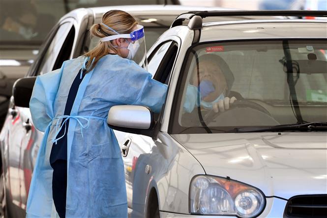 Nhân viên y tế lấy mẫu xét nghiệm COVID-19 cho người dân tại bang Victoria, Australia ngày 19-8-2021. Ảnh: AFP/TTXVN