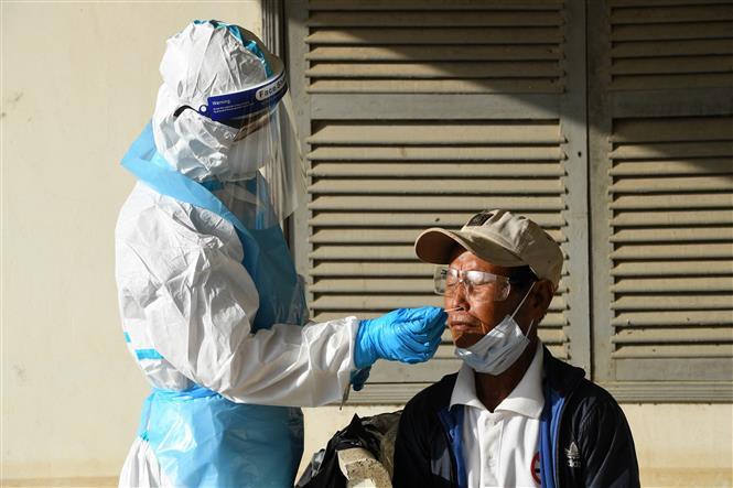 Nhân viên y tế lấy mẫu xét nghiệm COVID-19 cho người dân tại Phnom Penh, Campuchia ngày 16-8-2021. Ảnh: AFP/TTXVN
