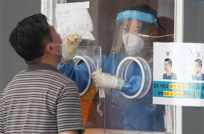 Nhân viên y tế lấy mẫu xét nghiệm COVID-19 tại Seoul, Hàn Quốc, ngày 15-8-2021. Ảnh: YONHAP/TTXVN