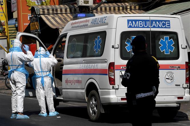 Nhân viên y tế chuyển bệnh nhân COVID-19 tới bệnh viện tại Phnom Penh, Campuchia, ngày 19-3-2021. Ảnh: AFP/ TTXVN
