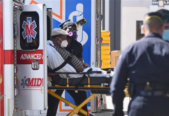 Nhân viên y tế chuyển bệnh nhân COVID-19 tới trung tâm y tế tại New York, Mỹ. Ảnh: AFP/ TTXVN