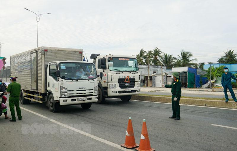 Xe chở hàng hóa qua chốt kiểm dịch cầu Rạch Miễu. Ảnh: A.Nguyệt