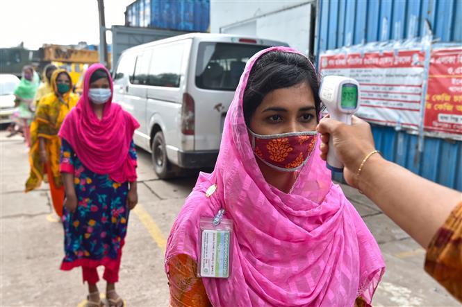 Kiểm tra thân nhiệt phòng lây nhiễm COVID-19 trước khi vào nhà máy ở Dhaka, Bangladesh, ngày 23-8-2021. Ảnh: THX/ TTXVN