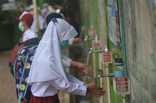 Học sinh rửa tay trước khi vào lớp nhằm ngăn chặn sự lây lan dịch COVID-19 tại một trường học ở Jakarta, Indonesia, ngày 30-8-2021. Ảnh: THX/TTXVN
