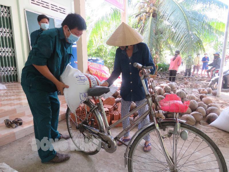 Đoàn thể, chính quyền địa phương hỗ trợ người dân nhận gạo tại Nhà văn hóa ấp Đông Thuận - Thanh Hòa.