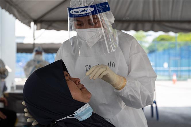 Nhân viên y tế lấy mẫu xét nghiệm COVID-19 cho người dân tại Kuala Lumpur, Malaysia . Ảnh: AFP/TTXVN