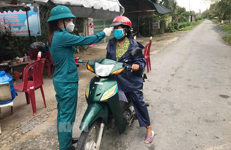 Chị Nguyễn Thị Ngọc Diệu đo thân nhiệt cho người dân tại chốt kiểm dịch Covid-19. Ảnh: Đặng Thạch
