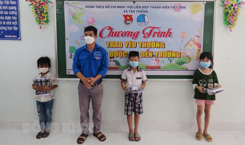 Các em học sinh có hoàn cảnh khó khăn nhận quà tại điểm Trường Tiểu học Tân Thiềng A. Ảnh: Lê Đệ