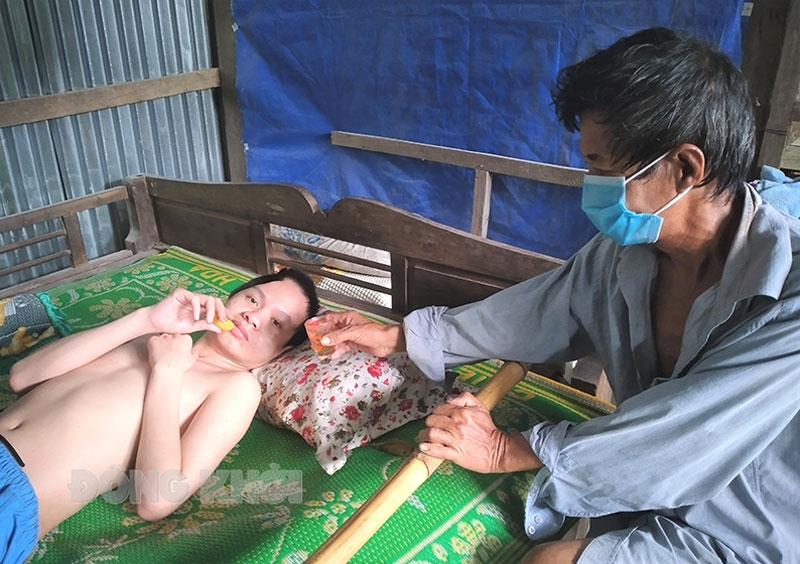 Ông Ngô Văn Đắng chăm sóc con trai bị tai nạn phải nằm một chỗ. Ảnh: H. Trâm