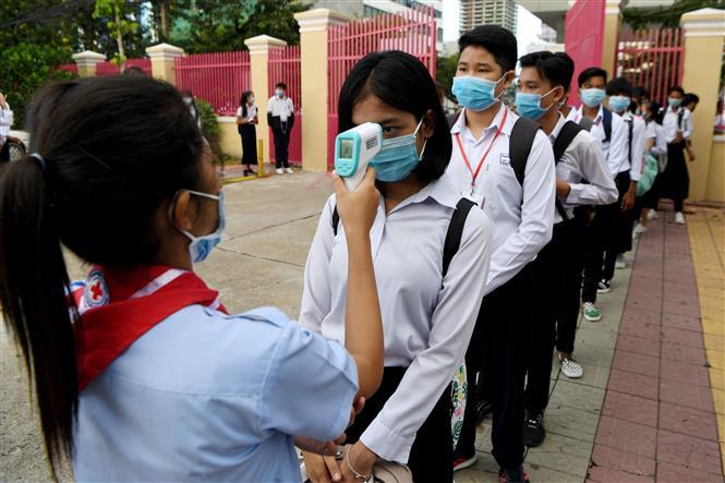 Học sinh đeo khẩu trang và được đo thân nhiệt để phòng lây nhiễm COVID-19 tại một trường học ở Phnom Penh, Campuchia. Ảnh: AFP/TTXVN