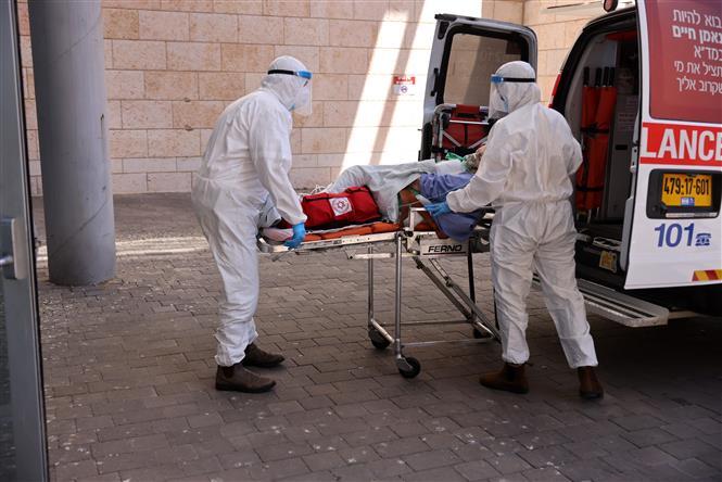Nhân viên y tế chuyển bệnh nhân COVID-19 tới bệnh viện ở Jerusalem, ngày 15-8-2021. Ảnh: AFP/ TTXVN
