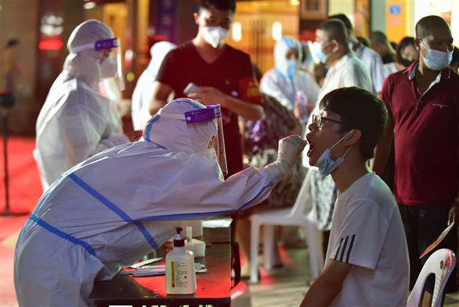 Nhân viên y tế lấy mẫu xét nghiệm COVID-19 cho trẻ em tại Phúc Kiến, Trung Quốc, ngày 12-9-2021. Ảnh: THX/ TTXVN
