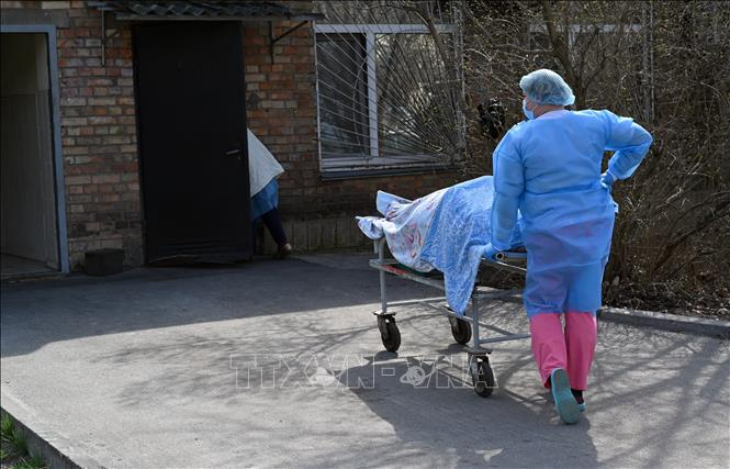 Chuyển bệnh nhân tử vong do COVID-19 tới nhà xác bệnh viện ở Kiev, Ukraine. Ảnh: AFP/TTXVN