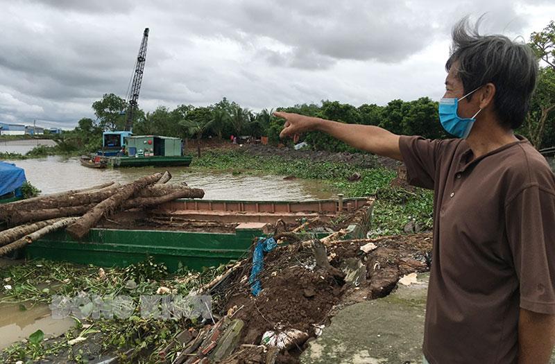 Ông Nguyễn Tấn Bang (xã Vĩnh Bình, huyện Chợ Lách) chỉ về phần đất của gia đình mình bị trôi xuống sông.