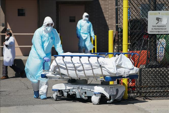 Nhân viên y tế chuyển bệnh nhân tử vong do COVID-19 tới nhà xác bệnh viện ở New York, Mỹ. Ảnh: AFP/TTXVN