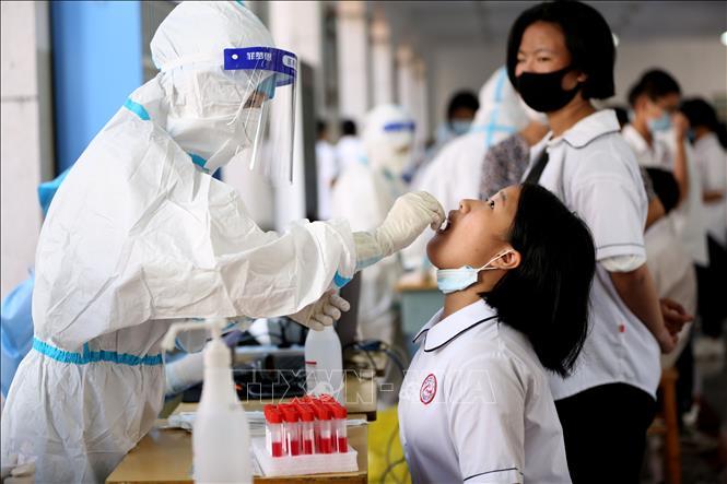 Nhân viên y tế lấy mẫu xét nghiệm COVID-19 tại một trường học ở tỉnh Phúc Kiến, Trung Quốc, ngày 15-9-2021. Ảnh: THX/TTXVN