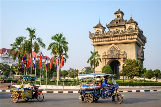 Người dân di chuyển trên đường phố tại Viêng Chăn, Lào. Ảnh: AFP/TTXVN