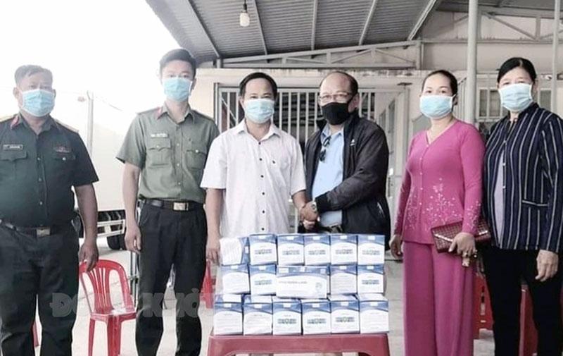 Thương binh Huỳnh Hữu Nghĩa (thứ 3, phải sang) trao khẩu trang y tế tại các chốt kiểm soát phòng chống dịch Covid-19. Ảnh: CTV