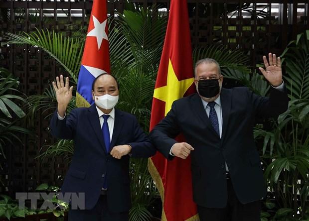 Chủ tịch nước Nguyễn Xuân Phúc và Thủ tướng Cộng hòa Cuba Manuel Marrero Cruz vẫy tay chào. Ảnh: Thống Nhất/TTXVN