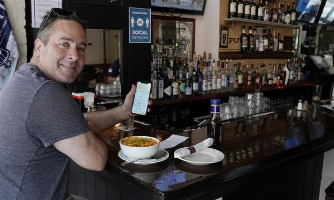 Khách hàng trình thẻ vaccine khi ăn trưa tại một nhà hàng ở New York, Mỹ. Ảnh: AFP/TTXVn