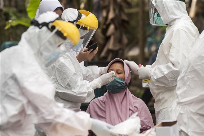 Nhân viên y tế lấy mẫu xét nghiệm COVID-19 cho người dân tại Yogyakarta, Indonesia, ngày 14-6-2021. Ảnh: THX/ TTXVN