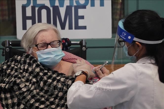 Nhân viên y tế tiêm vaccine COVID-19 của hãng Pfizer cho người cao tuổi tại New York, Mỹ. Ảnh: AFP/TTXVN