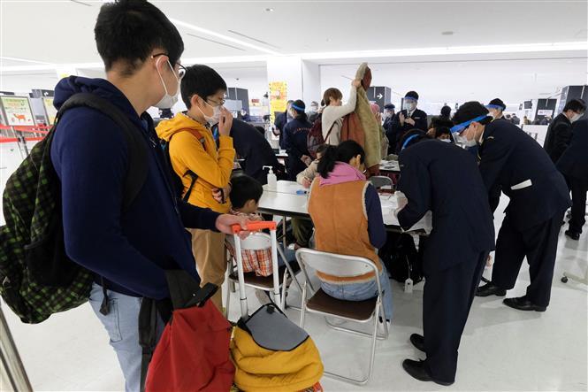 Hành khách điền thông tin vào phiếu cách ly phòng dịch COVID-19 tại sân bay quốc tế Narita, tỉnh Chiba, Nhật Bản. Ảnh: AFP/ TTXVN