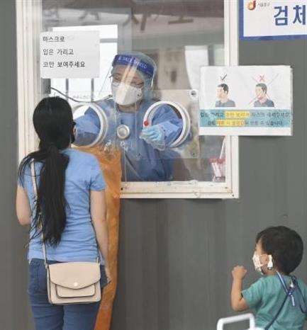 Nhân viên y tế lấy mẫu xét nghiệm COVID-19 cho người dân tại Seoul, Hàn Quốc ngày 25-9-2021. Ảnh: Kyodo/TTXVN