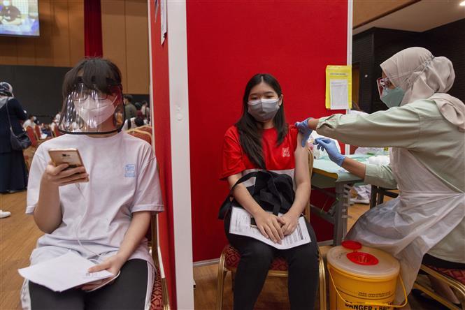 Nhân viên y tế tiêm vaccine ngừa COVID-19 cho học sinh tại Shah Alam, bang Selangor, Malaysia. Ảnh: THX/TTXVN