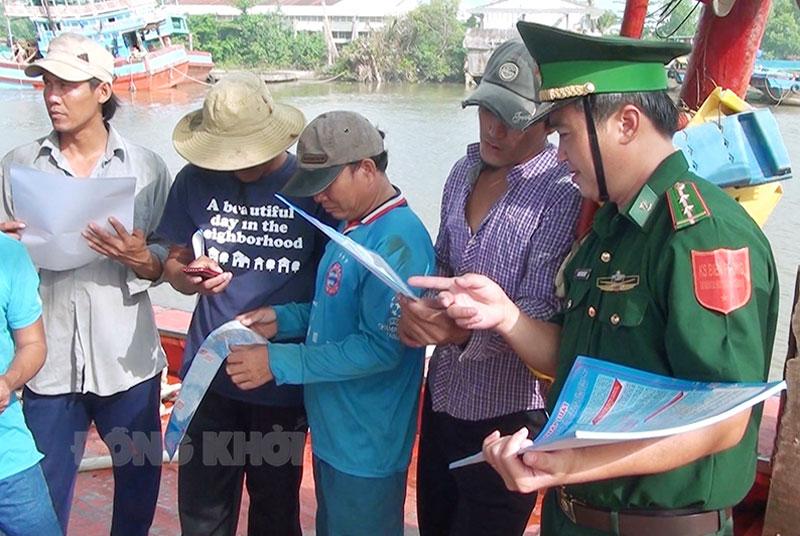 Cán bộ Trạm Kiểm soát Biên phòng Bình Thắng phát tờ rơi tuyên truyền thực hiện Nghị định số 42/NĐ-CP xử lý khai thác thủy sản vi phạm vùng biển nước ngoài.