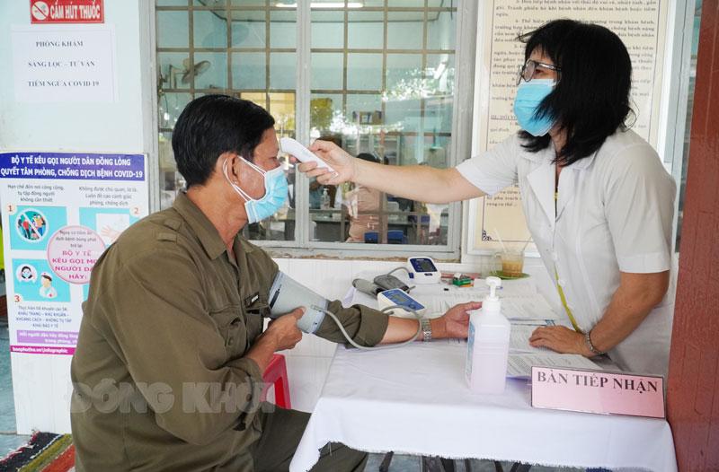 Cán bộ y tế làm nhiệm vụ sàng lọc trước tiêm chủng.
