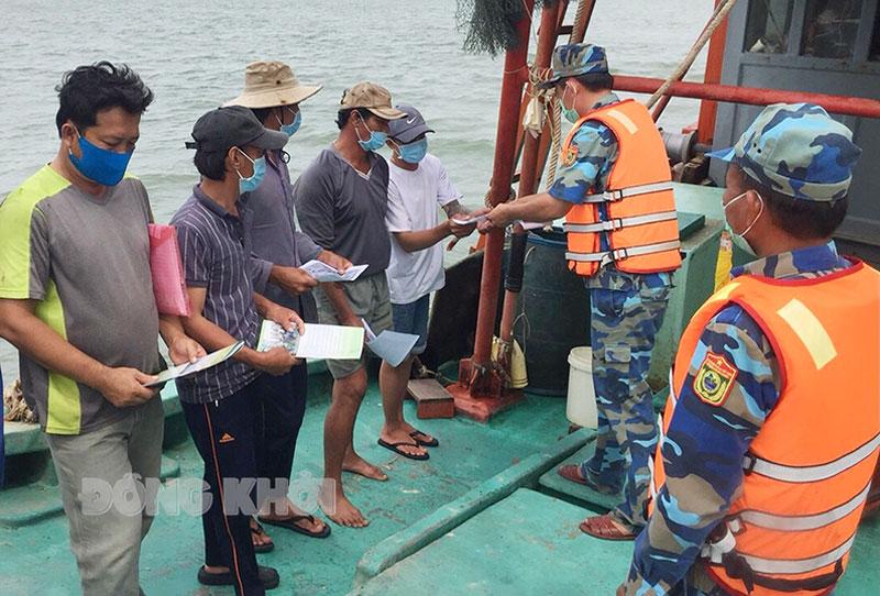 Cán bộ Hải đội Biên phòng 2 phát tờ rơi tuyên truyền phòng chống dịch Covid-19 cho ngư dân. Ảnh: P. Khánh