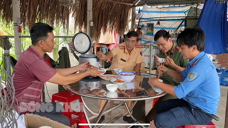 Lực lượng làm nhiệm vụ tại chốt kiểm soát cầu Cổ Chiên quây quần bên mâm cơm tại gia đình ông Nguyễn Văn Hùng.