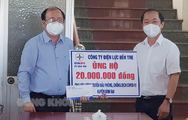 Giám đốc Công ty Điện lực Bến Tre Phạm Thanh Trúc trao tặng bảng biểu trưng ủng hộ lực lượng tuyến đầu phòng chống dịch Covid-19 huyện Bình Đại.